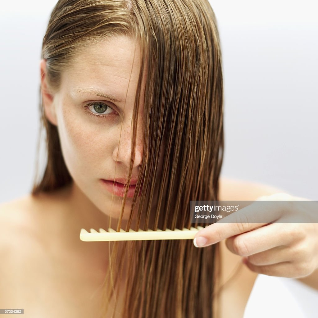 Portrait of a young woman combing her hair : Stock Photo