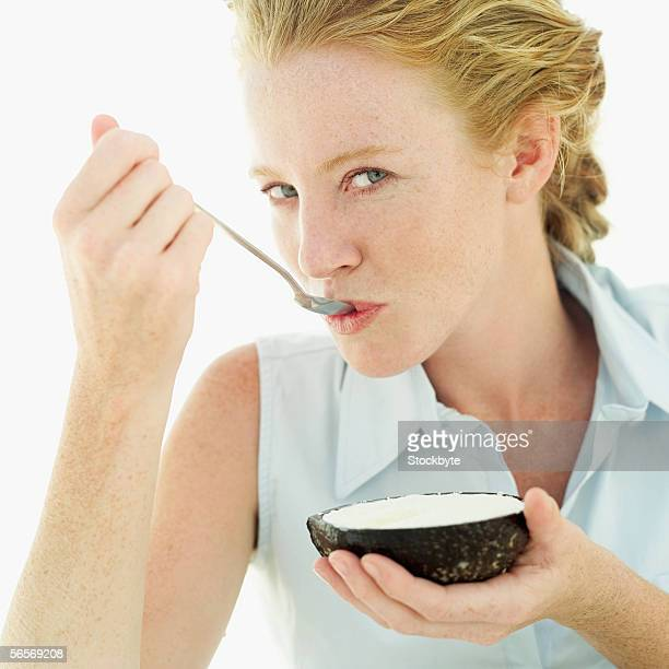 portrait of a young woman eating a grated coconut with a spoon