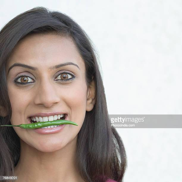 Portrait of a young woman eating a green chili