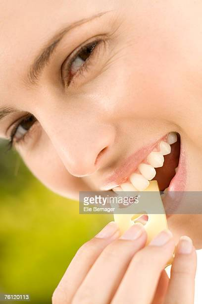 Portrait of a young woman eating a piece of gruyere cheese, outdoors