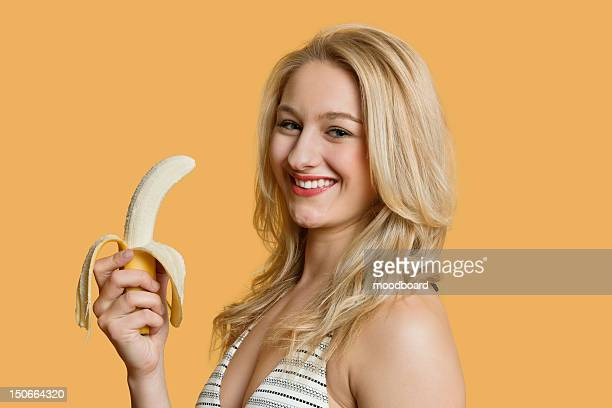 Portrait of a young woman eating banana over colored background