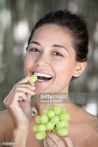 Portrait of a young woman eating grapes