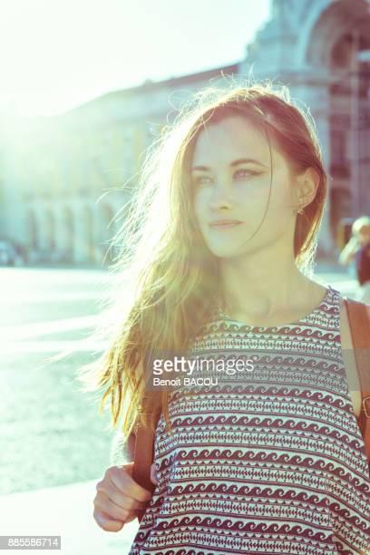 Portrait of a young woman face, against the light, on the Place du Commerce, Lisbon, Portugal