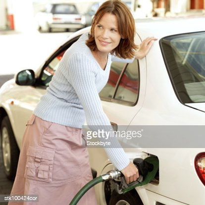 portrait of a young woman filling her car with petrol : Stock Photo