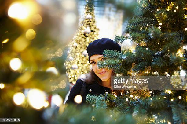 portrait of a young woman hiding between decorated christmas trees looking into the camera