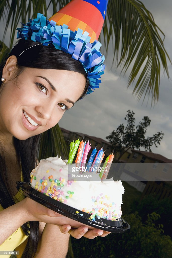 Portrait of a young woman holding a birthday cake and smiling : Stock Photo