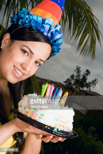 Portrait of a young woman holding a birthday cake and smiling : Foto de stock