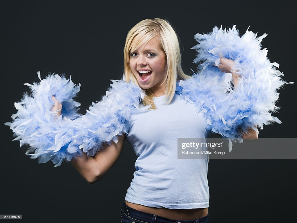 Portrait of a young woman holding a feather boa around her neck and smiling