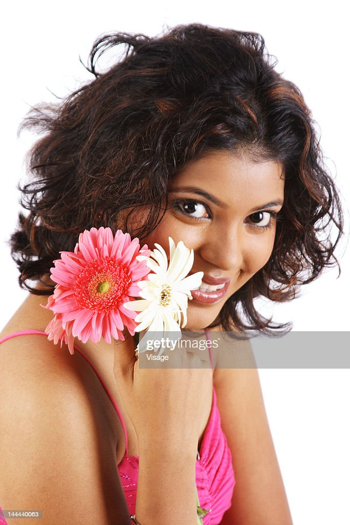 A portrait of a young woman holding a flower : Stock Photo