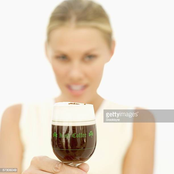 Portrait of a young woman holding a glass of Irish coffee