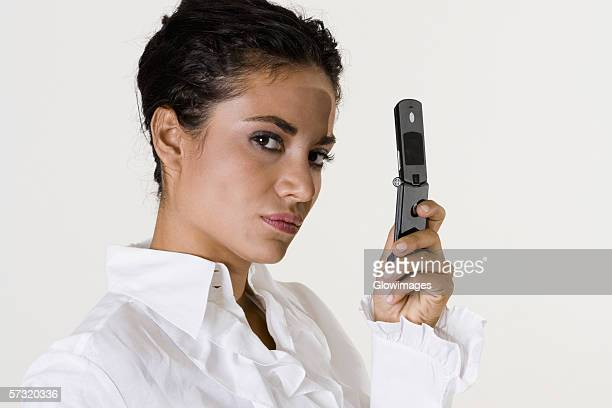 Portrait of a young woman holding a mobile phone