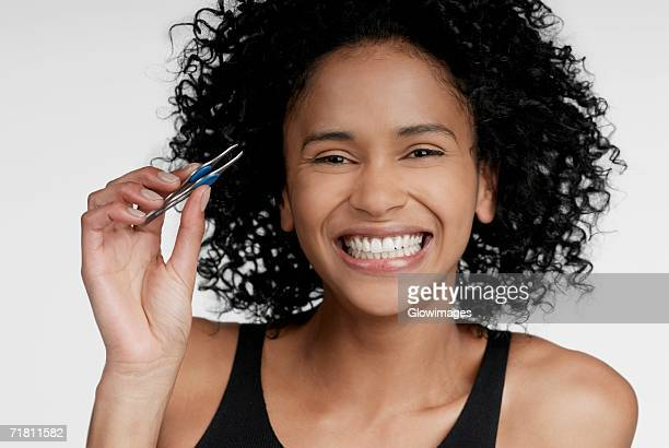 Portrait of a young woman holding a pair of eyebrow tweezers