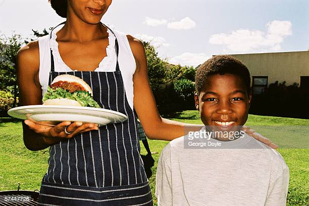 portrait of a young woman holding a plate of food and standing with her son