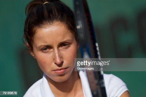 Portrait of a young woman holding a tennis racket : Foto de stock
