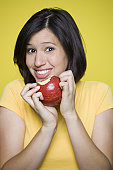 Portrait of a young woman holding an apple