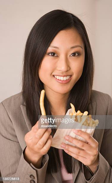 Portrait of a young woman holding French fries and smiling