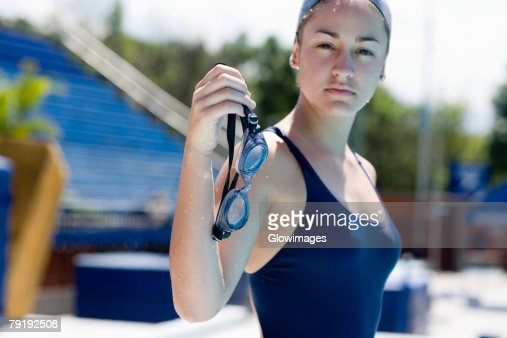 Portrait of a young woman holding her swimming goggles : Foto de stock