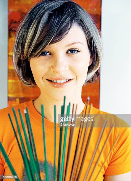 Portrait of a young woman holding incense sticks looking at camera smiling