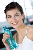 Portrait of a young woman holding mineral water bottle