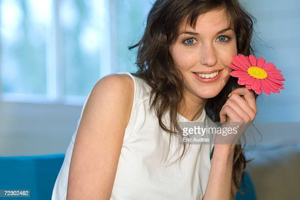 Portrait of a young woman holding plastic flower, smiling for the camera