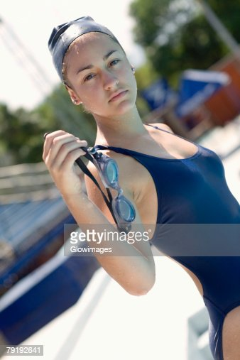 Portrait of a young woman holding swimming goggles : Stock Photo