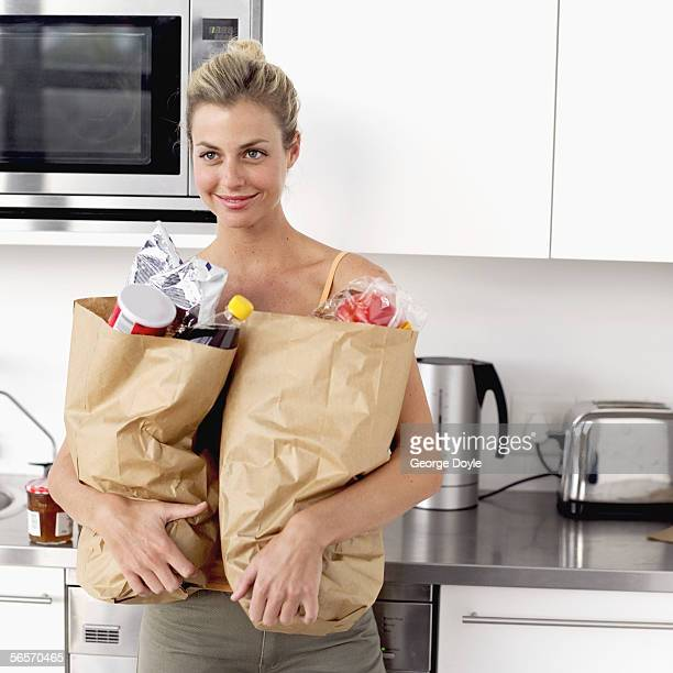 portrait of a young woman holding two brown paper grocery bags