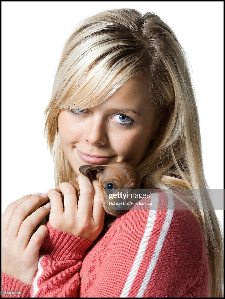 Portrait of a young woman hugging a puppy : Stock Photo
