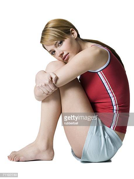 Portrait of a young woman hugging her knees