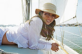 Portrait of a Young Woman in a Sunhat and Sunglasses Lying on the Deck of a Yacht