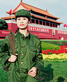 Portrait of a young woman in army uniform standing in front of a palace, Forbidden Palace, Beijing, China