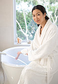 Portrait of a young woman in bathrobe filling bathtub with water