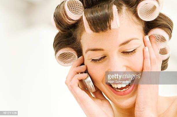 Portrait of a young woman in curlers phoning