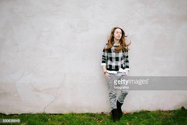 Porträt einer jungen Frau vor einer Betonwand