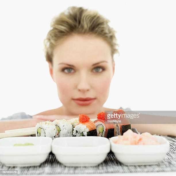 portrait of a young woman in front of sushi rolls and condiments