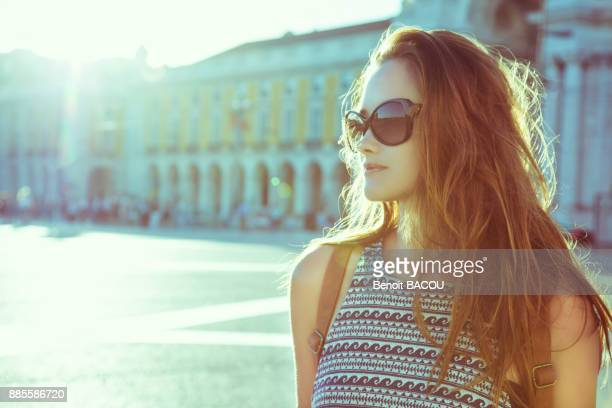 Portrait of a young woman in profile, against the light, on the Place du Commerce, Lisbon, Portugal