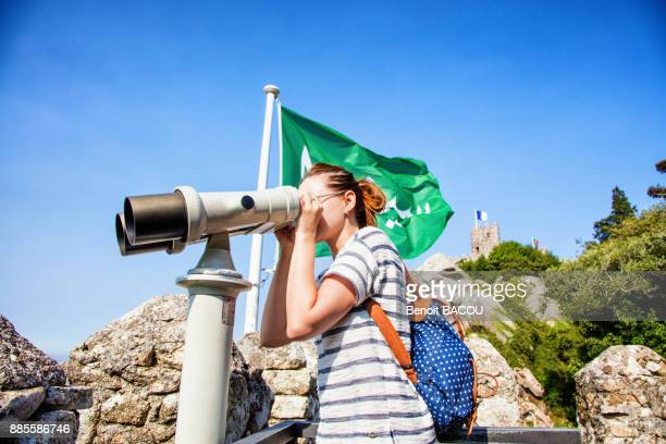 Portrait of a young woman in profile, looking at the Binocular Telescope on the walls of the Moorish castle, Sintra, Lisbon area, Portugal