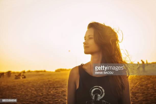 Portrait of a young woman in profile, on the beach Praia do Barril in a sunset, deTavira city, region of Algarve, Portugal