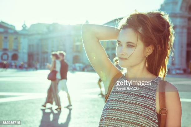 Portrait of a young woman in profile, one hand behind his head, against the light, on the Place du Commerce, Lisbon, Portugal