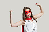 Portrait of a young woman in super hero costume flexing muscles over gray background