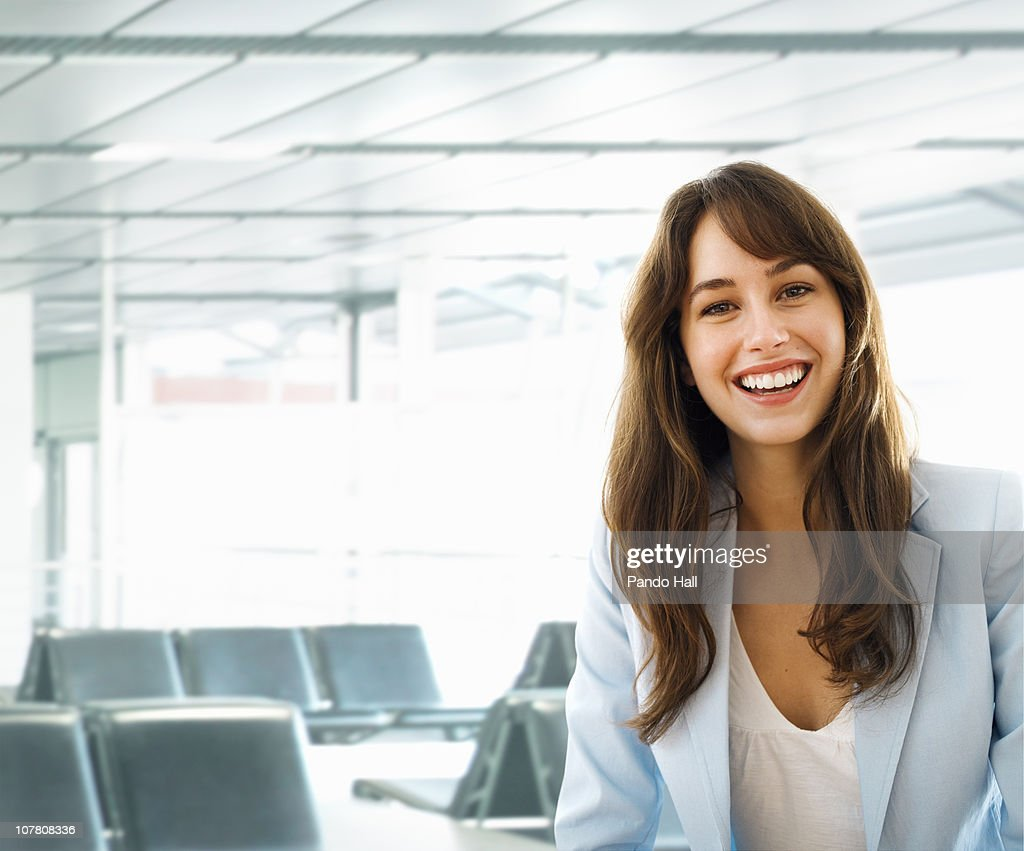 Portrait of a young woman in waiting area, smiling : Stock Photo