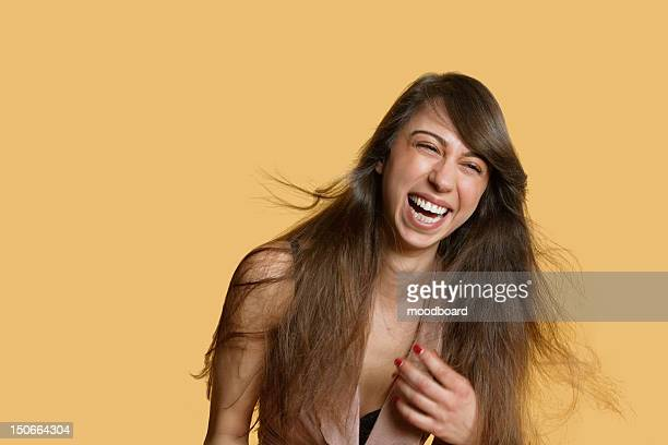 Portrait of a young woman laughing over colored background
