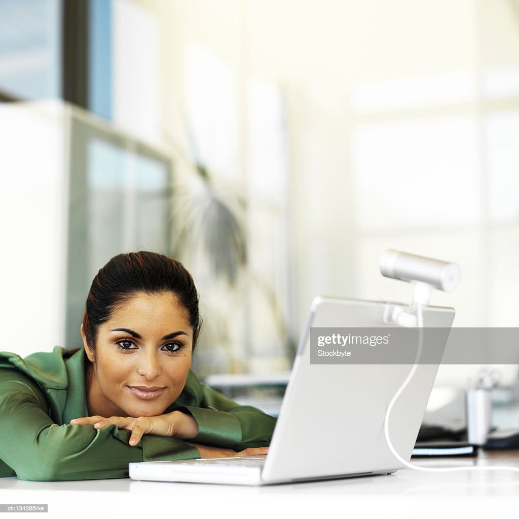 portrait of a young woman leaning forward on the table with a laptop in front of her : Stock Photo