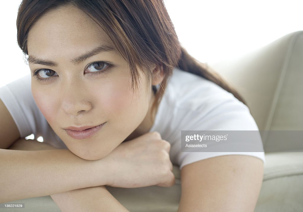 Portrait of a young woman leaning on a couch and smiling : Stock Photo