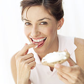 portrait of a young woman licking cream cheese off toast