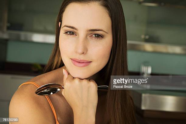 Portrait of a young woman looking at camera, holding spoon