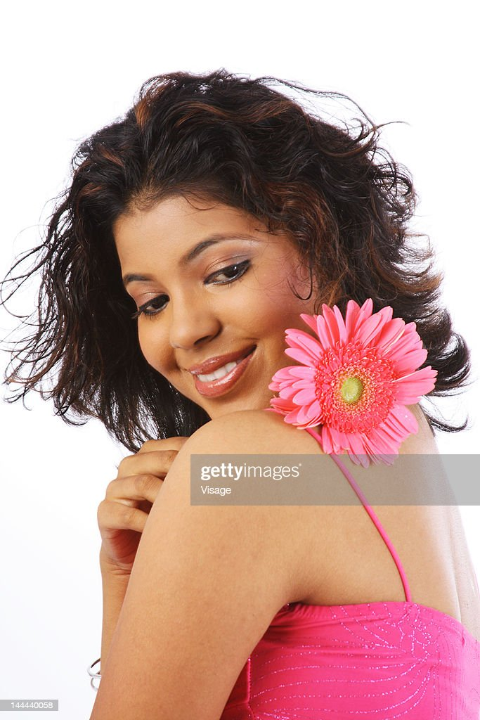 A portrait of a young woman looking over her shoulder, holding a flower : Stock Photo