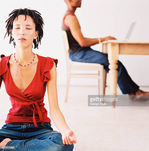 portrait of a young woman meditating cross legged on the floor