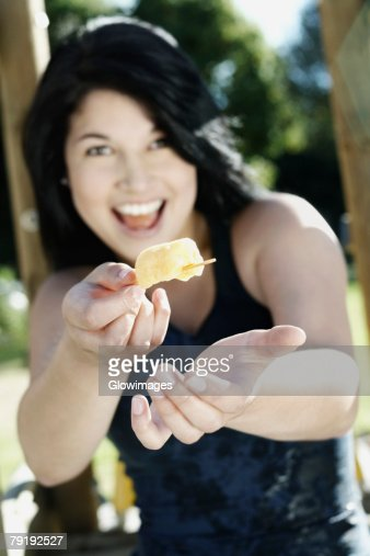 Portrait of a young woman offering an ice candy : Foto de stock