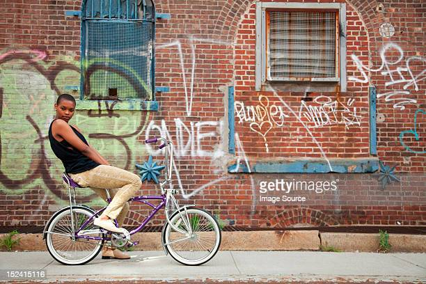 Portrait of a young woman on bicycle by wall covered in graffiti