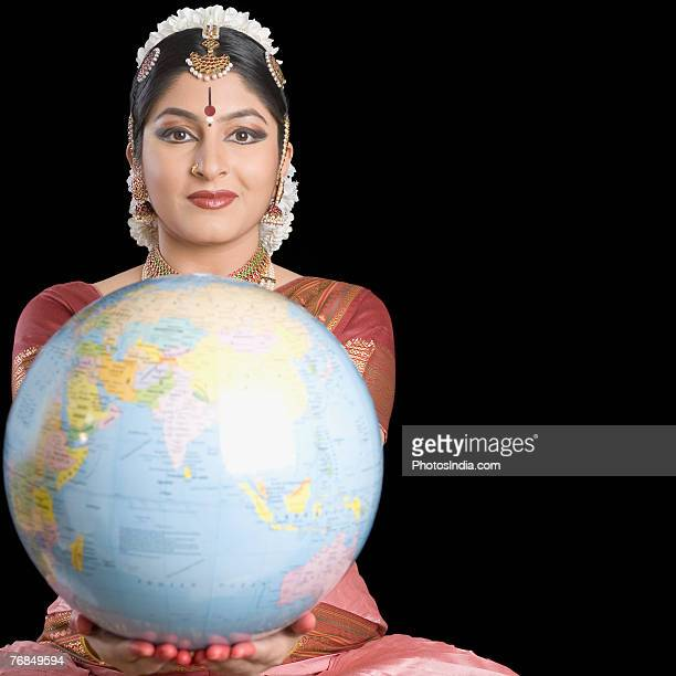 Portrait of a young woman performing Bharatnatyam and holding a globe